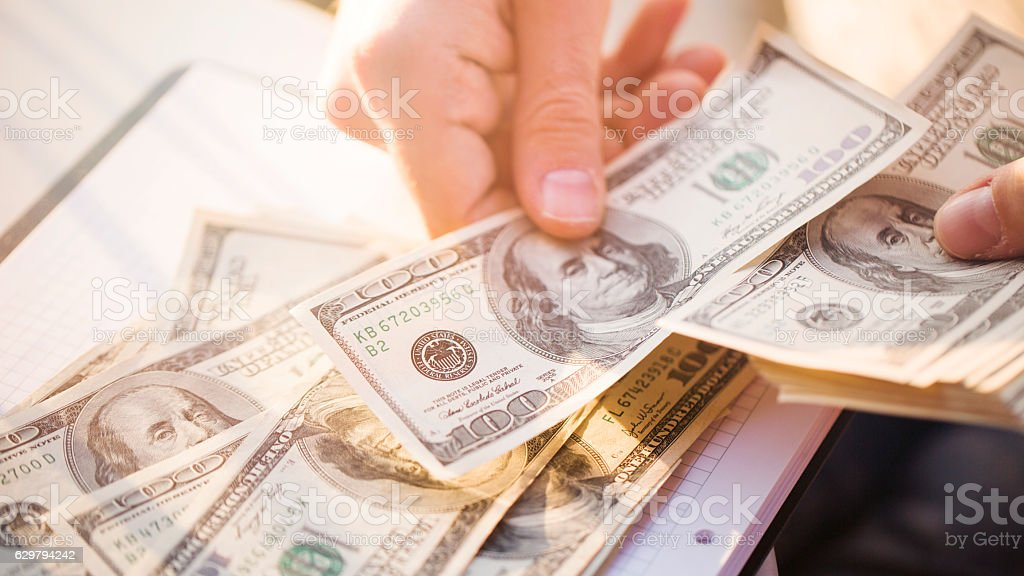 Hands counting us dollars with calculator and digital tablet royalty-free stock photo