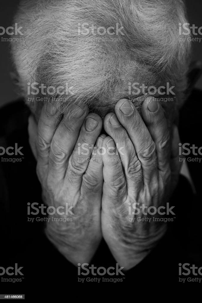 Hands covering face of old man stock photo