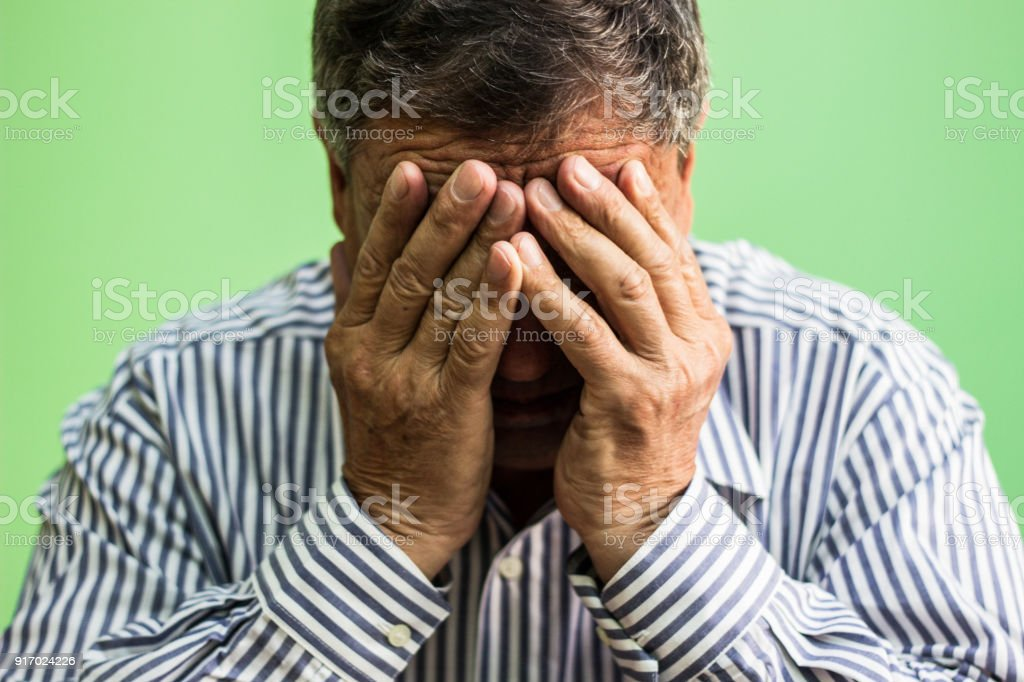 Hands covering face of senior man stock photo