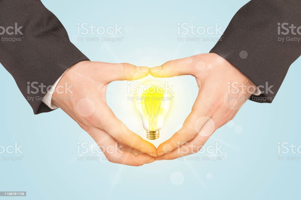 Hands creating a form with yellow light bulb in the center