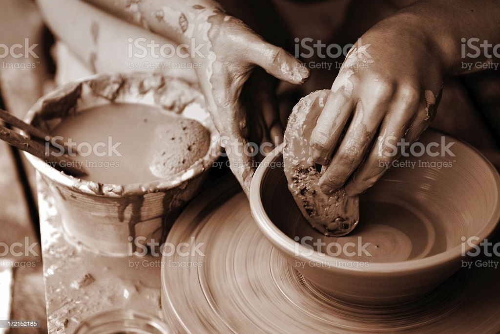 Hands creating a pottery bowl on a wheel stock photo