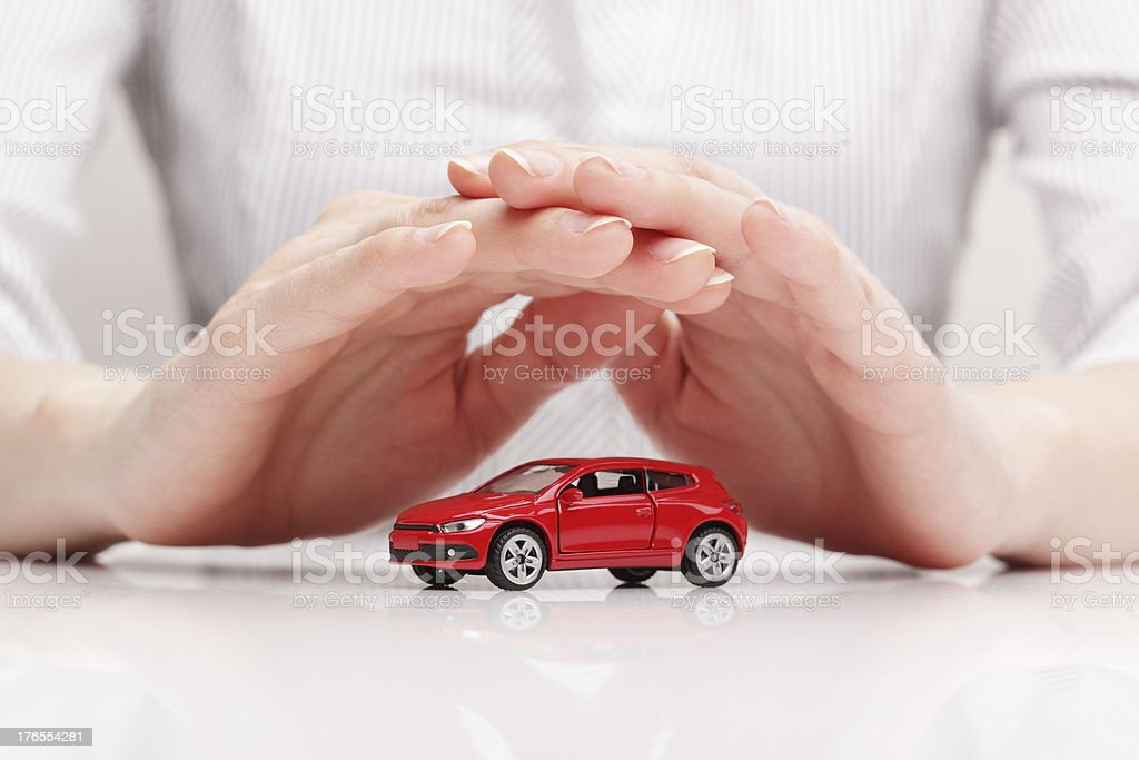 Hands creating protective shield over small car stock photo