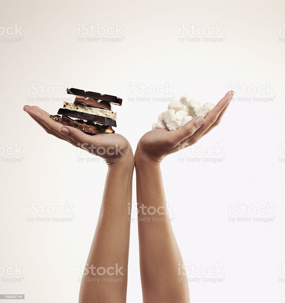 Hands cupping chocolate bars and sugar cubes stock photo