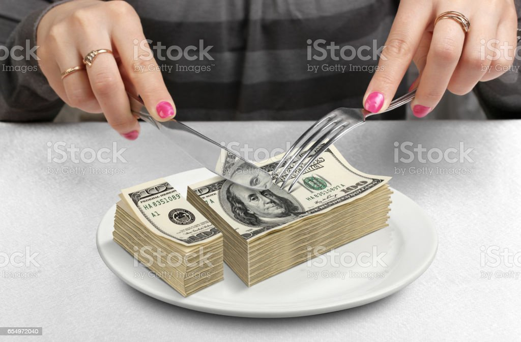 Hands cut money on plate, reduce funds concept stock photo
