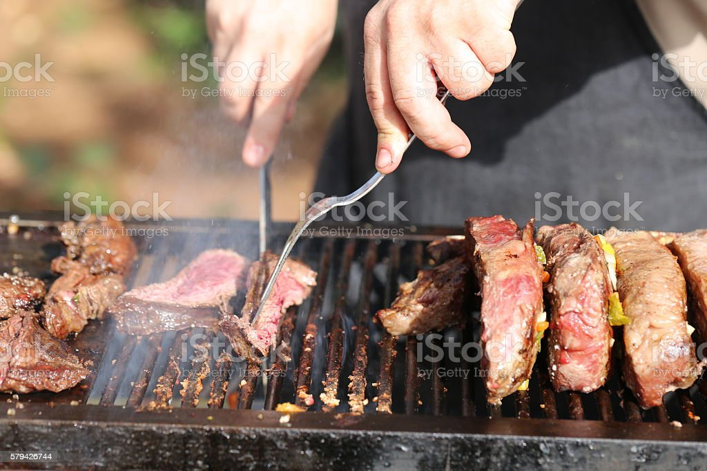 Hands Cutting Meat With Grill Tools - foto de stock