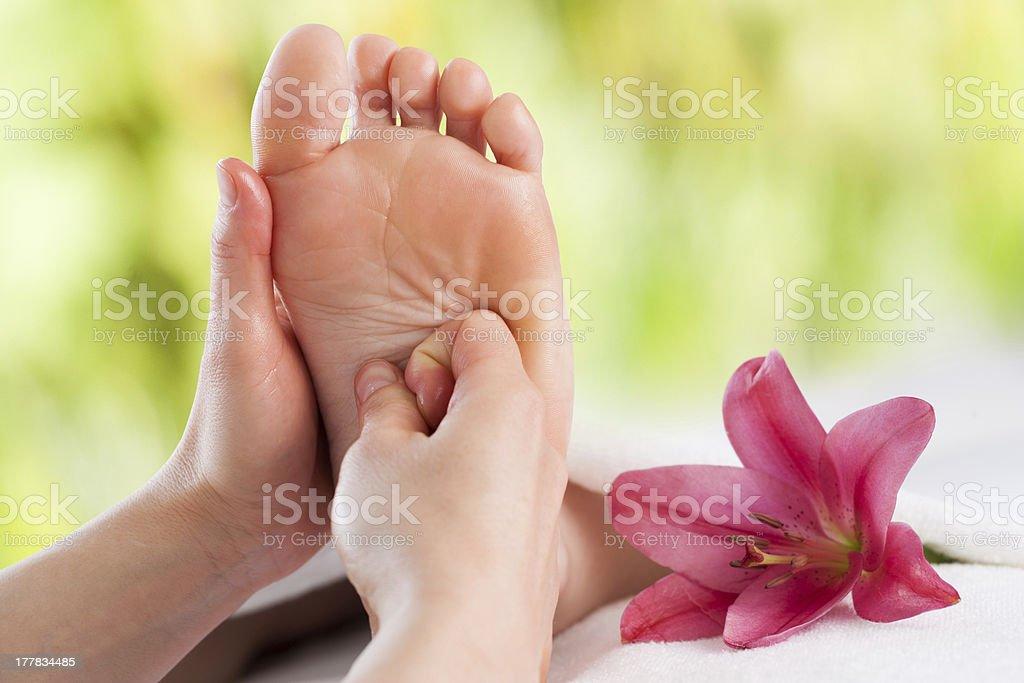 Hands doing foot reflexology. stock photo