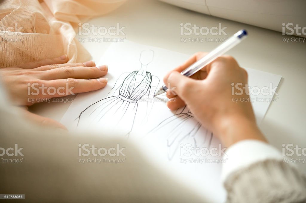 Hands drawing a clothing design sketch stock photo