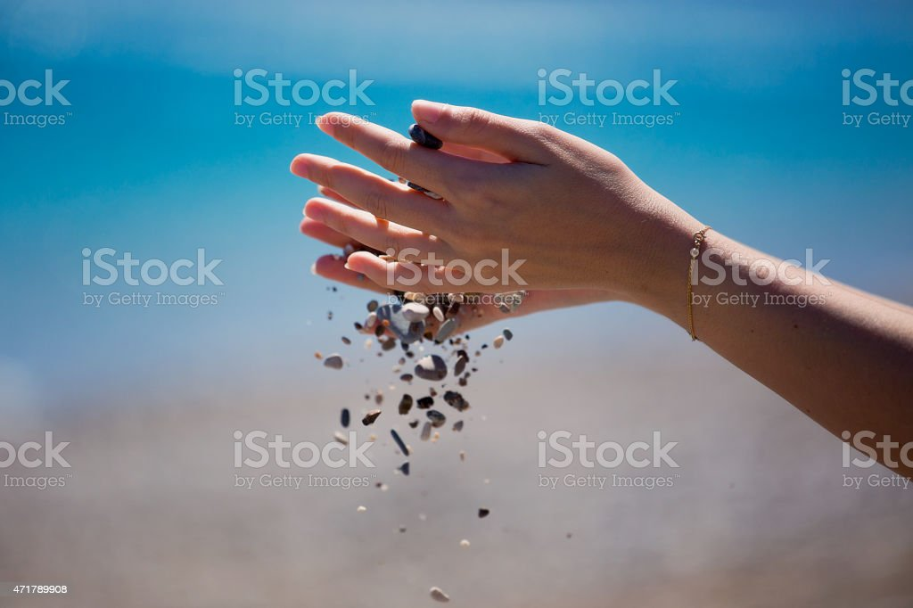 Hands dropping small stones stock photo
