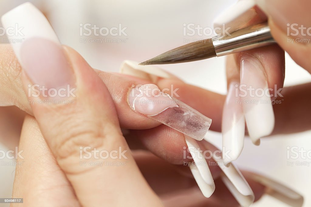 Hands during nail modeling stage of acrylic manicure process royalty-free stock photo