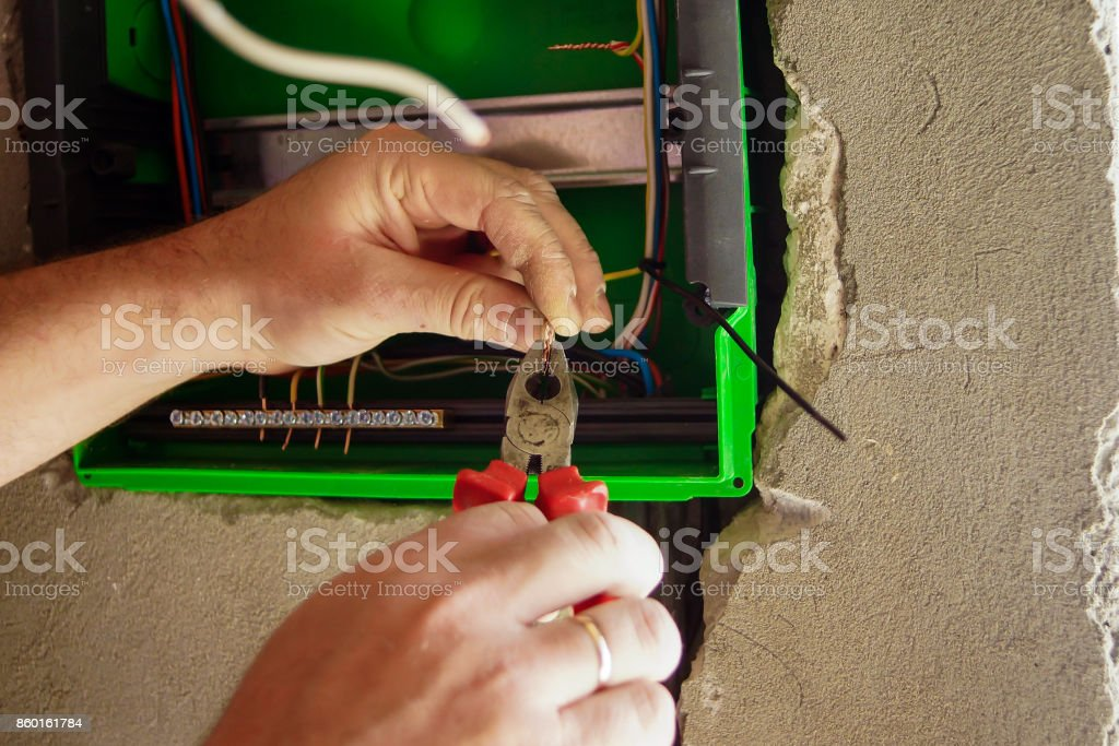 Excellent Hands Electrical Wiring Is Pulled Through The Hole In The Wall Of Wiring Digital Resources Bemuashebarightsorg