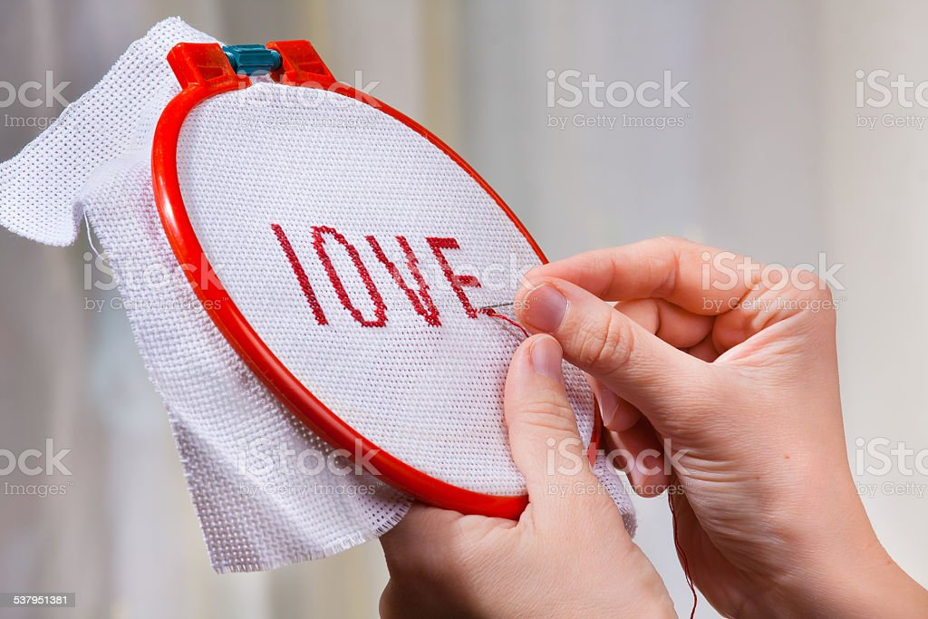 hands embroider a word love stock photo