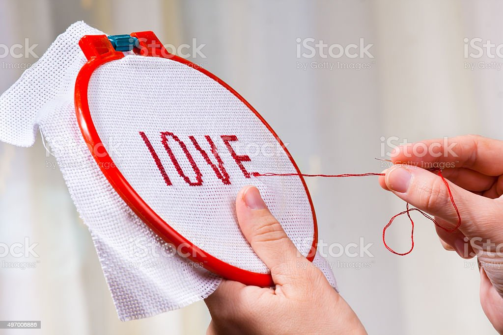 hands embroider cross-stitch a word love stock photo
