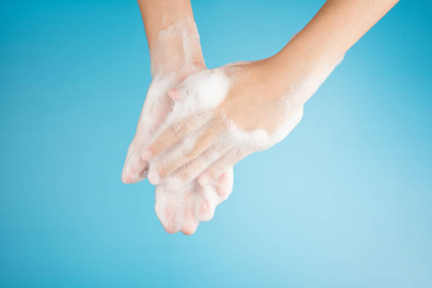 Hands female washing with bubble foam from soap on top view isolated on blue background stock photo