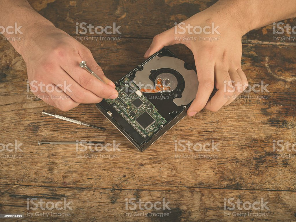 Hands fixing a harddrive on desk stock photo