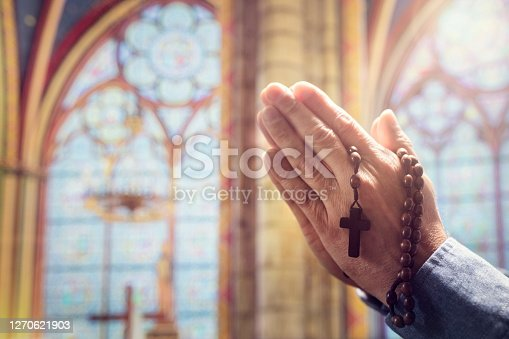 istock Hands folded in prayer in church with rosary beads and religious cross 1270621903