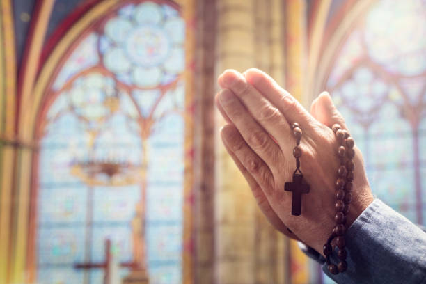 Hands folded in prayer in church with rosary beads and religious cross stock photo