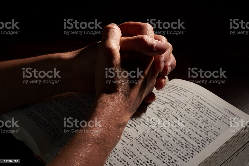 hands folded on open bible stock photo
