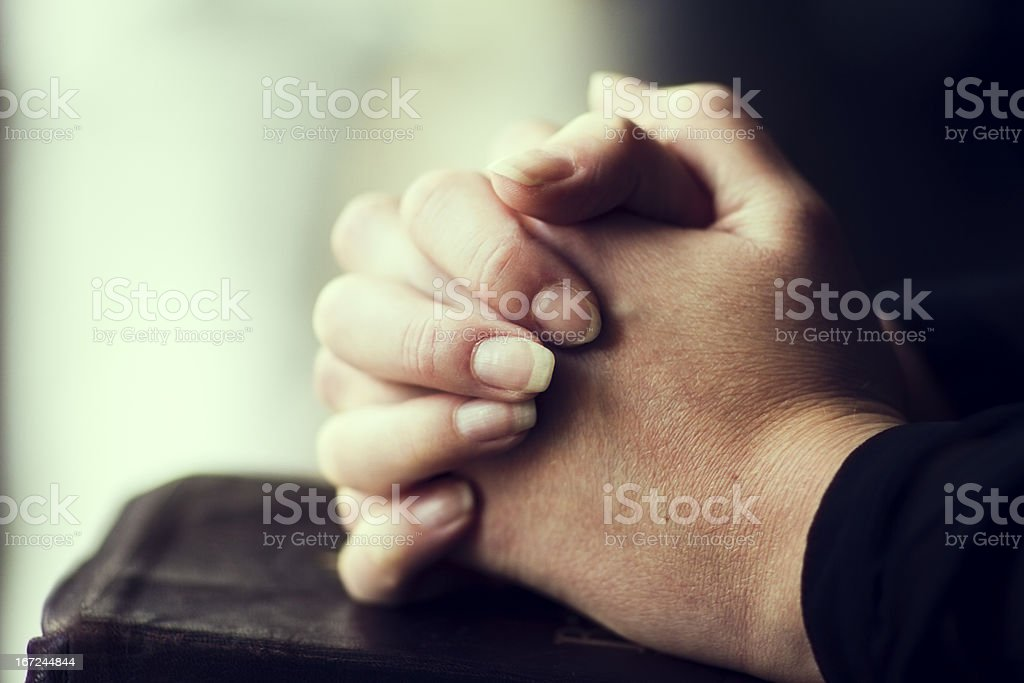 Hands folded together on leather Bible stock photo