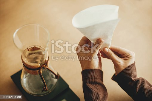 Hands folding paper filter for pour over and glass kettle on scale on brown background. Preparing for alternative coffee brewing v60. Fold coffee filter