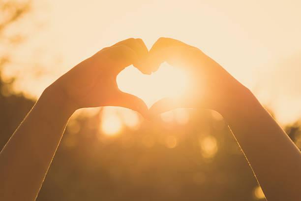 Hände bilden ein Herz-Form bei Sonnenuntergang – Foto