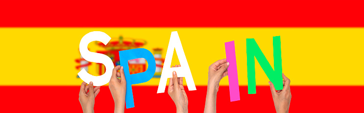 hands forming  Spain text with flag background