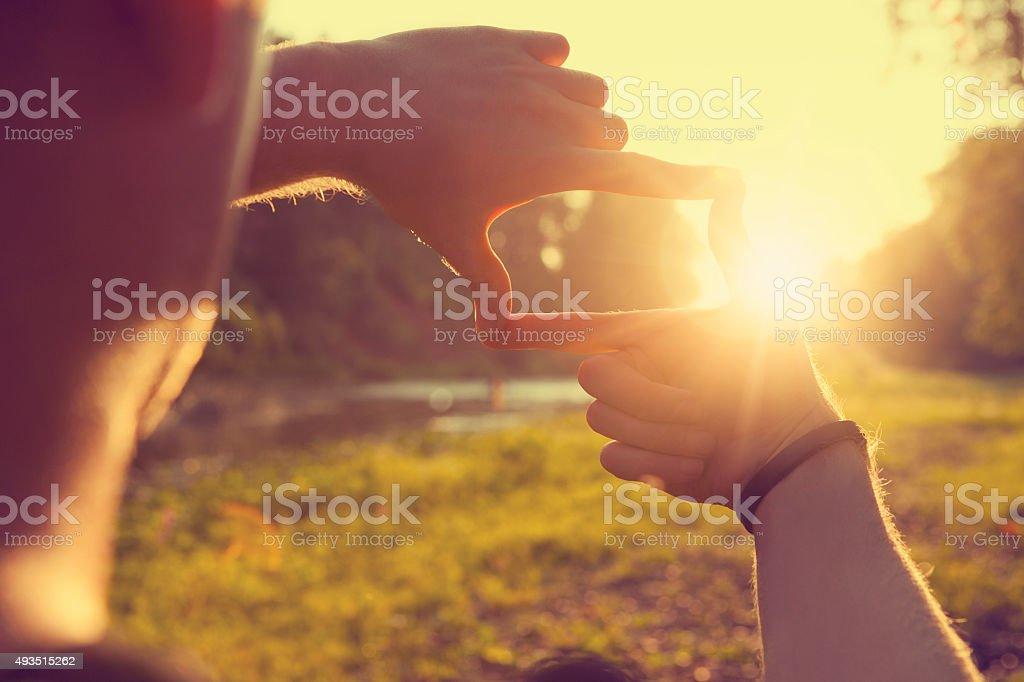 Ręce framing odległy słońca promieni – zdjęcie