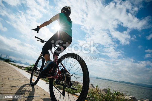 istock Hands free cycling female riding mountain bike on seaside 1139819021