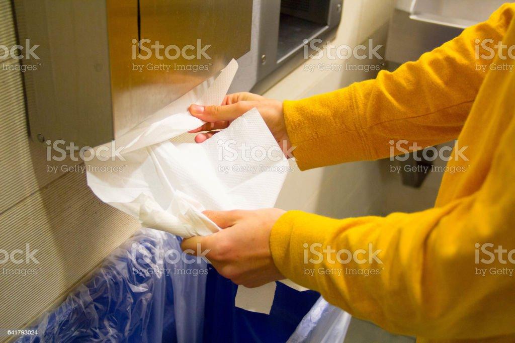 Hands Getting Paper Towel in Bathroom stock photo