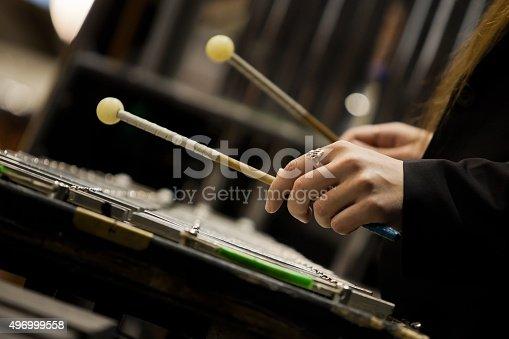 Hands girl playing a glockenspiel in dark colors closeup