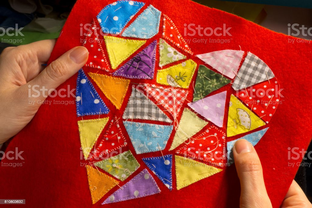 Hands girls embroider abstract patterns of heart from multicolored embroidered patches on red cloth. Embroidery. Women's hobby. Creative work. Love, romance and creativity stock photo