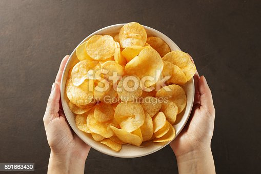 istock Hands giving bowl of potato chips on brown background. 891663430