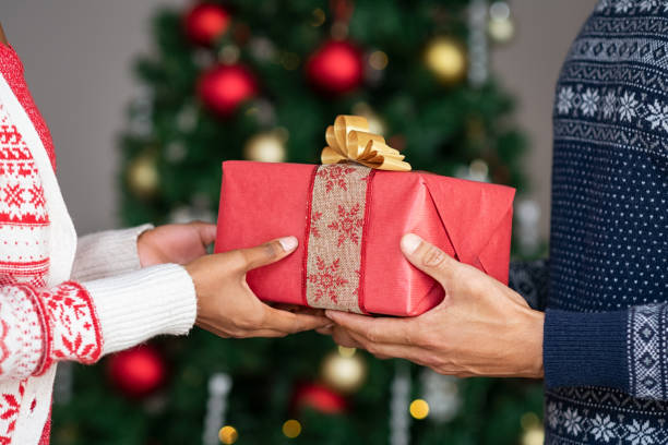 Hands giving christmas gifts Couple wearing christmas theme sweater exchanging gifts in front of decorated christmas tree. Closeup of african woman hand receive xmas present from her boyfriend. Young couple holding christmas gift. exchanging stock pictures, royalty-free photos & images