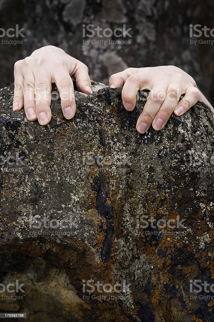 Hands grasp hold of the rock stock photo