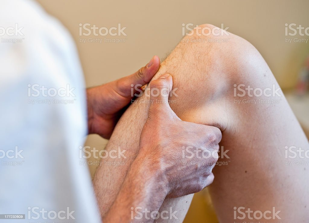 Hands gripped around knee and calf royalty-free stock photo