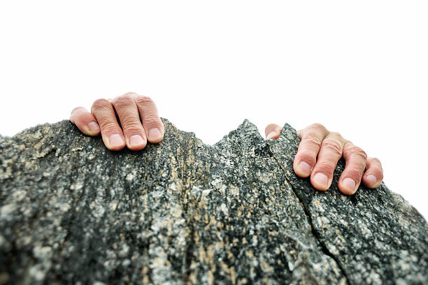 Hands Gripping the Rock Summit stock photo