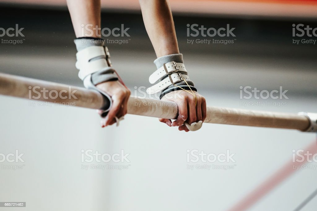 hands grips athletes female gymnast exercises on uneven bars stock photo