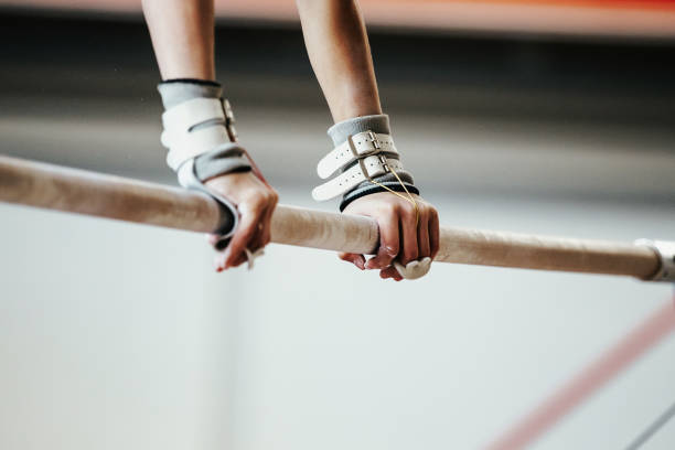 hands grips athletes female gymnast exercises on uneven bars - balance beam stock photos and pictures