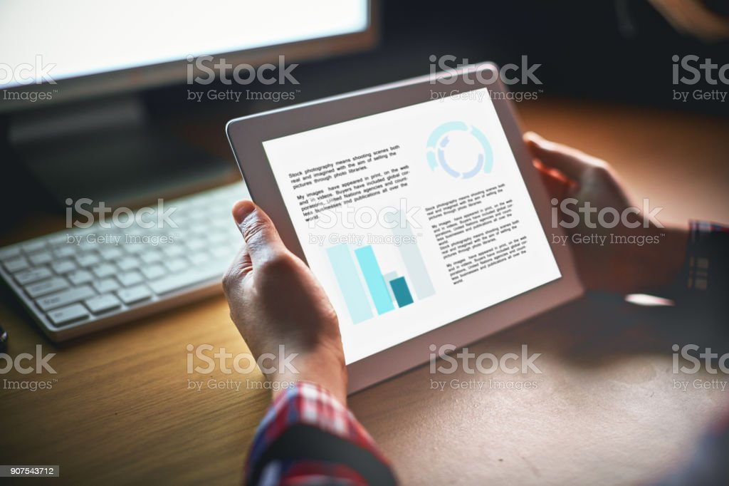 Hands hold a digital tablet with unrecognizable information, at night stock photo