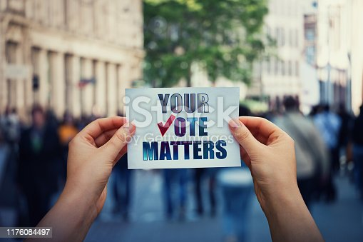 1157022917 istock photo Hands hold a paper sheet with the message your vote matters over a crowded street background. People legal and democratic rights, every voice counts. Election campaign and electoral agitation concept 1176084497
