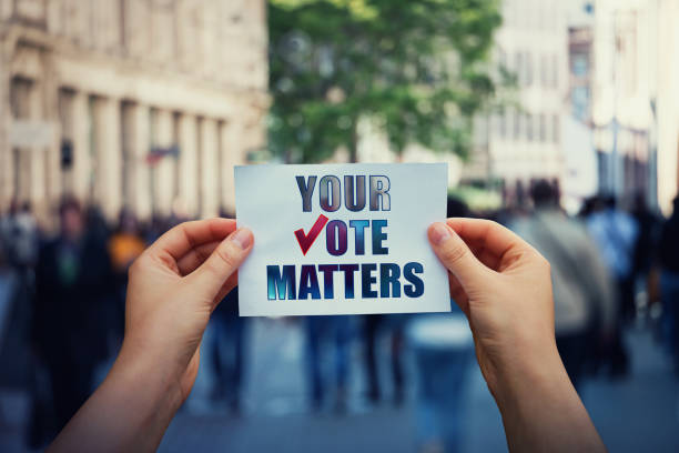 hands hold a paper sheet with the message your vote matters over a crowded street background. people legal and democratic rights, every voice counts. election campaign and electoral agitation concept - vote стоковые фото и изображения