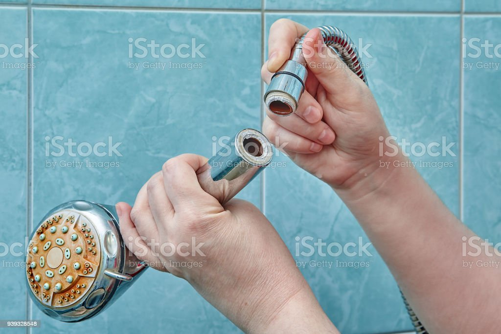 Hands hold a shower head that broke off from hose. stock photo