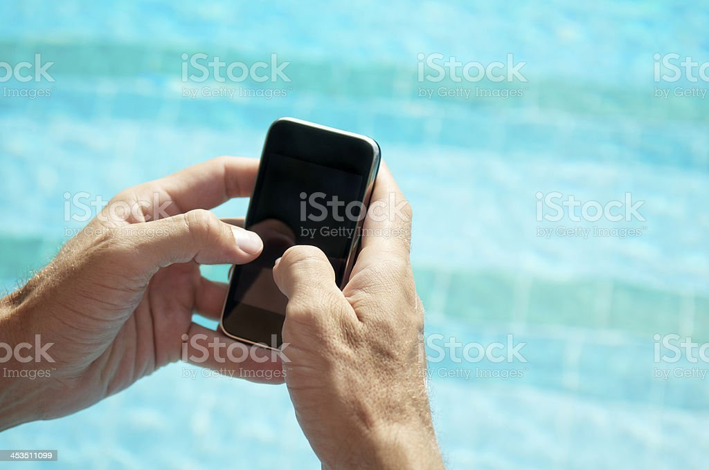 Hands Hold Blank Smartphone Mobile Phone at Swimming Pool royalty-free stock photo