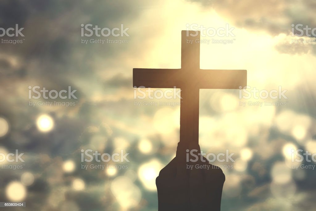 Hands hold crucifix symbol stock photo