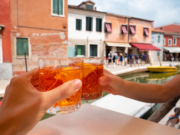 Hands hold glasses of spritz cocktails with ice to make cheers in Burano, the city with colorful houses in Venice, Italy stock photo