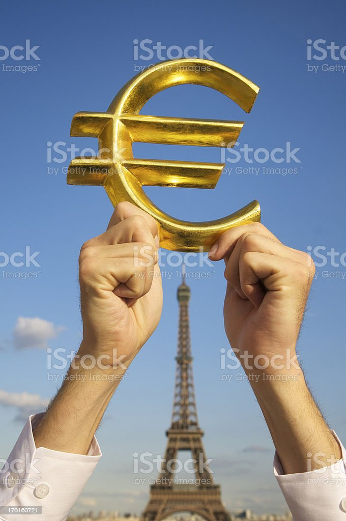 Hands Hold Golden Euro Currency Symbol by Eiffel Tower royalty-free stock photo