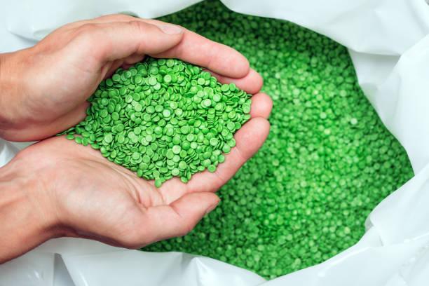 hände halten oder berühren biologisch abbaubare kunststoffpellets, kunststoff-polymer-granulat - polypropylen stock-fotos und bilder