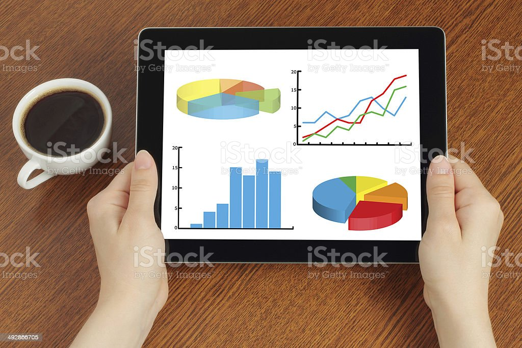 Hands hold tablet PC with graphs stock photo