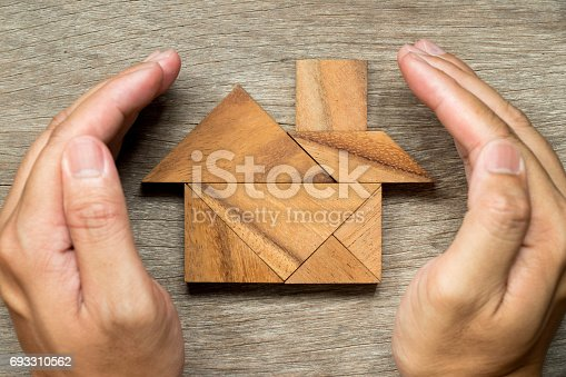 istock Hands hold the tangram puzzle in home shape (Concept for Home protection or insurance) 693310562