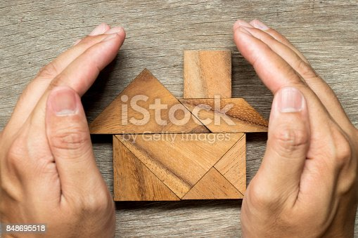 istock Hands hold the tangram puzzle in home shape (Concept for Home protection or insurance) 848695518
