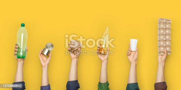 Hands hold trash on a yellow background. The concept of separate trash, stop plastic, recycling